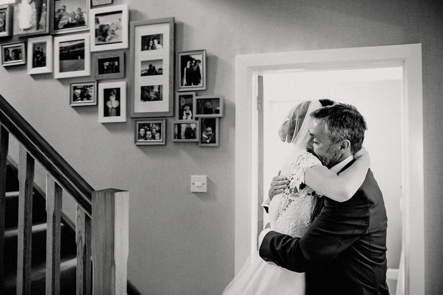 bride and dad hug at the bottom of the stairs