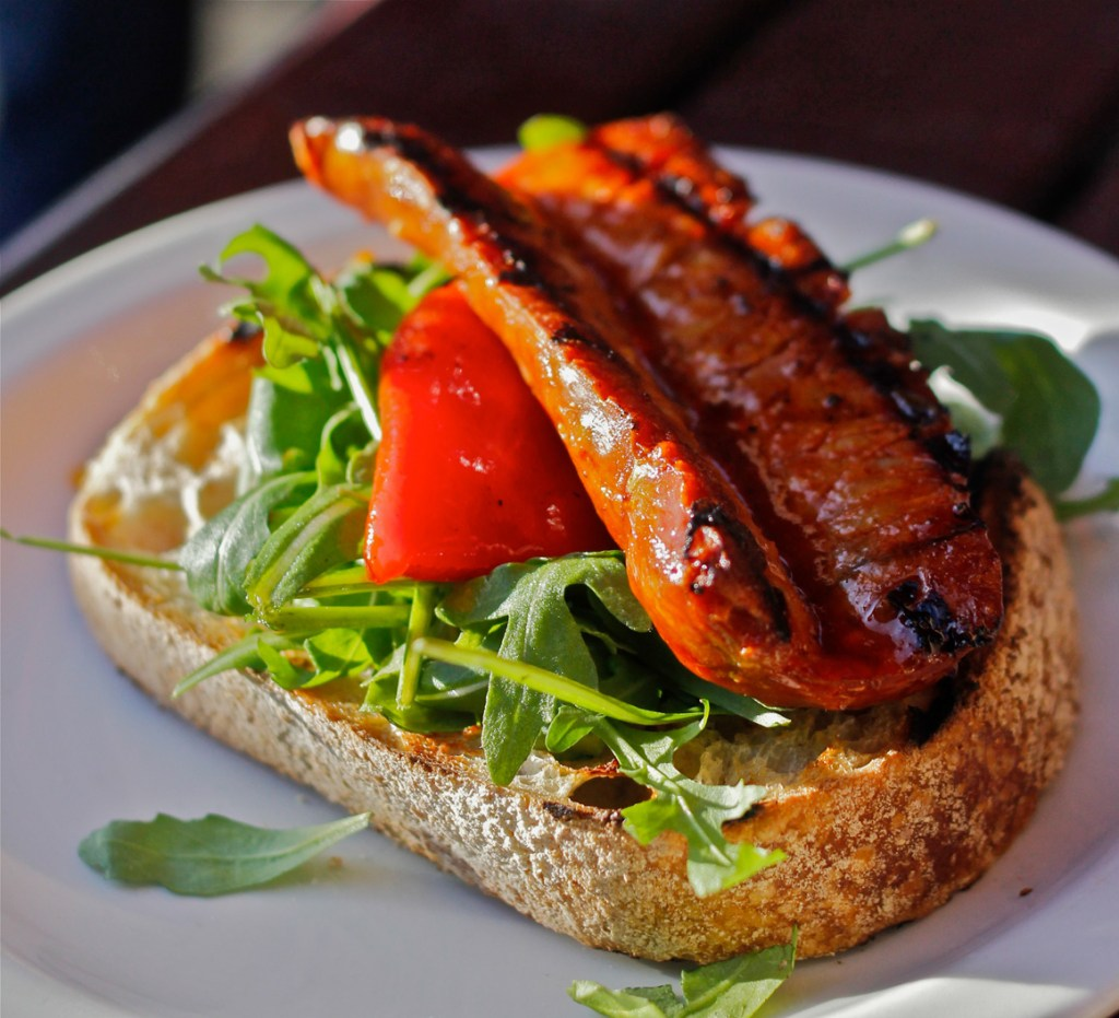 Grilled Chorizo, roquette, sweet pimento on ciabatta at Brindsa Foods