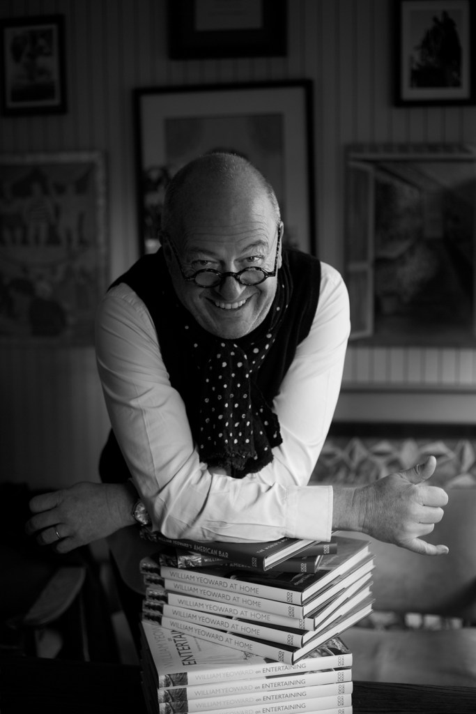 William Yeoward, Interior designer, leaning on stack of books, and laughing
