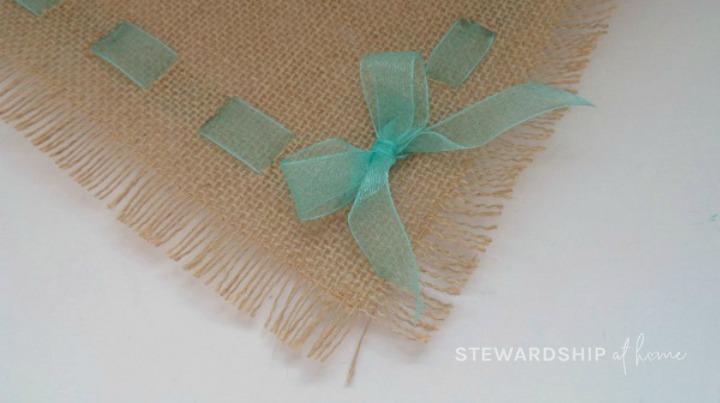 tie ribbon at corners of burlap and ribbon placemat