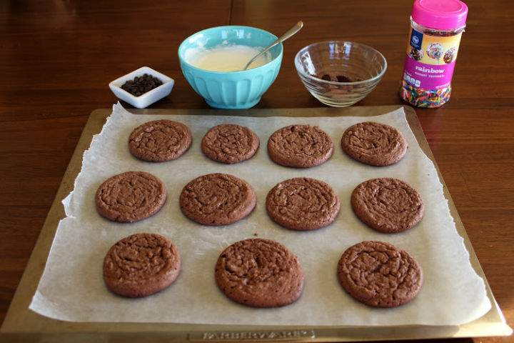 baked chocolate cookies on a cookie sheet with bowls of toppings