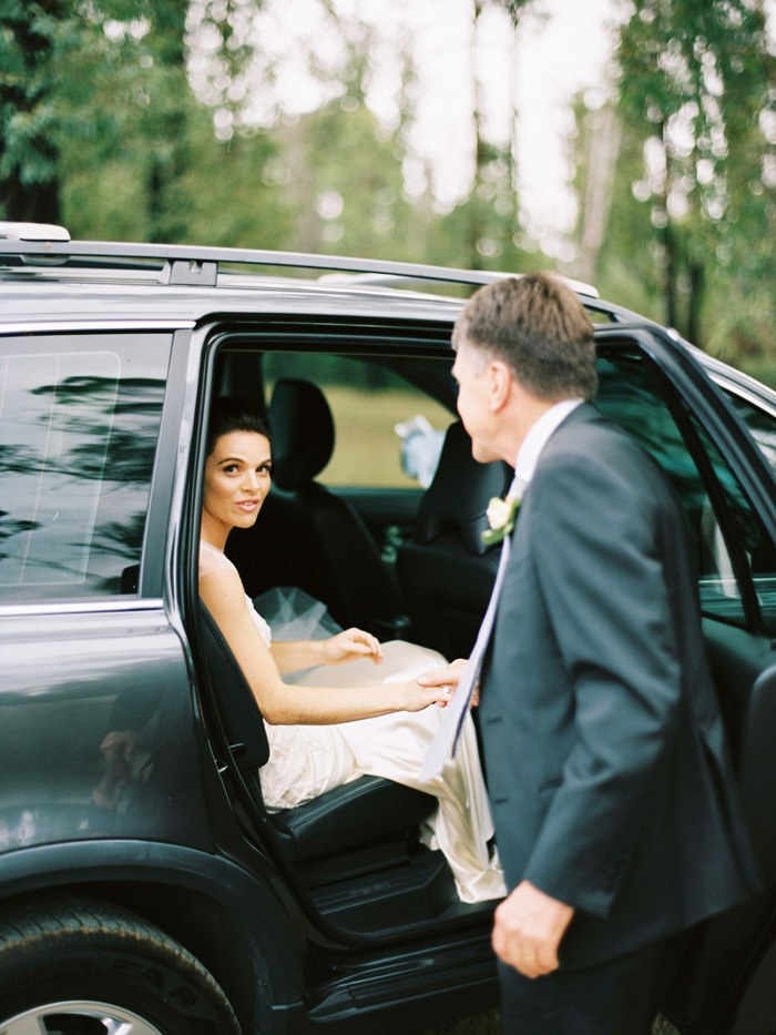 dad helping her daughter the bride get out of the bridal car