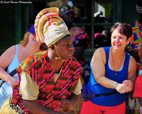 A member of Tam Tams, a West African rhythms and dance group, lead Walt Disney World guests in a dance.
