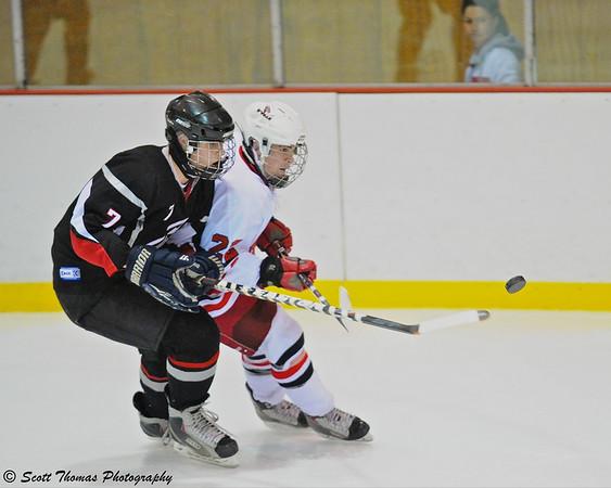 Baldwinsville's Matt Zandri (22) checks a Clarance Red Devils player in the Robert T. Conklin Memorial Tournament finals at the Greater Baldwinsville Ice Arena.