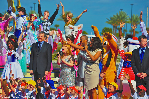 Disney CEO Bob Iger with Disney Dream Godmother, Jennifer Hudson (singing in tan dress) and Walt Disney Parks & Resorts chairman, Tom Staggs, on stage during the Disney Dream christening ceremony.