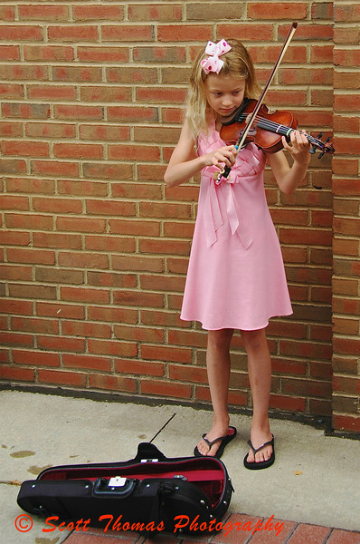 A young street performer playing her violin during the Kerrytown Farmers Market in Ann Arbor, Michigan.