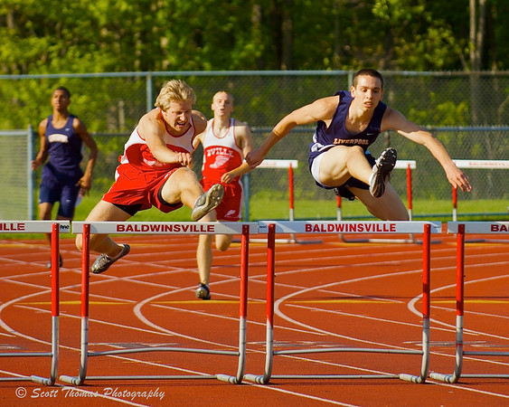 Runners jumping over the hurdles.