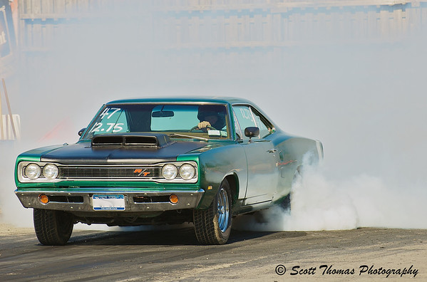 1968 Dodge Coronet R/T doing a long, smokey burnout heating up the rear tires to make them even stickier for the important start in the race.