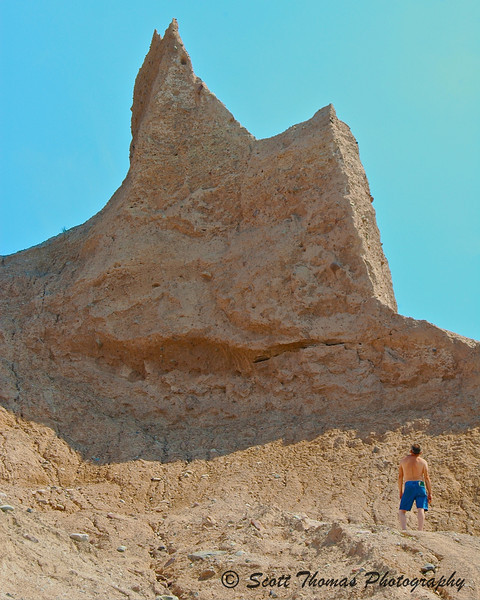 A lone hiker studies one of the tall stone pinnacles found in Chimney Bluffs State Park near Sodus, New York.