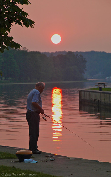 An elderly man fishing on the New York Barge Canal near Lock 24 in Baldwinsville, New York.