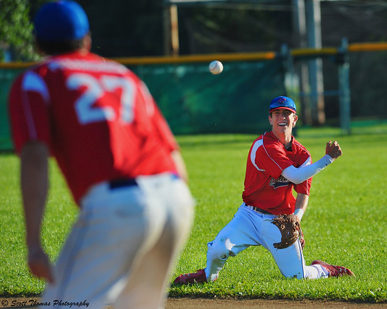From his knees, the second baseman throws the runner out at first base.