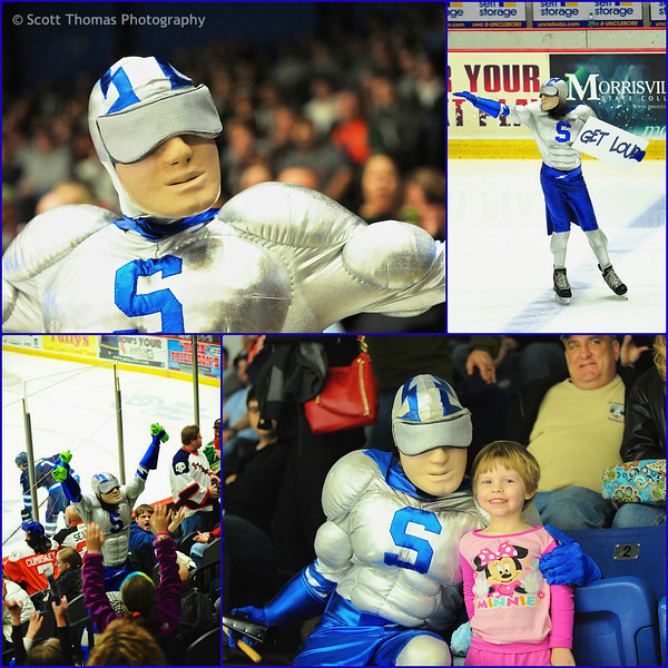 Crunchman, mascot for the Syracuse Crunch ice hockey team, poses for the camera, gets the crowd to make noise, throws free t-shirts to the crowd and meets with a young fan.