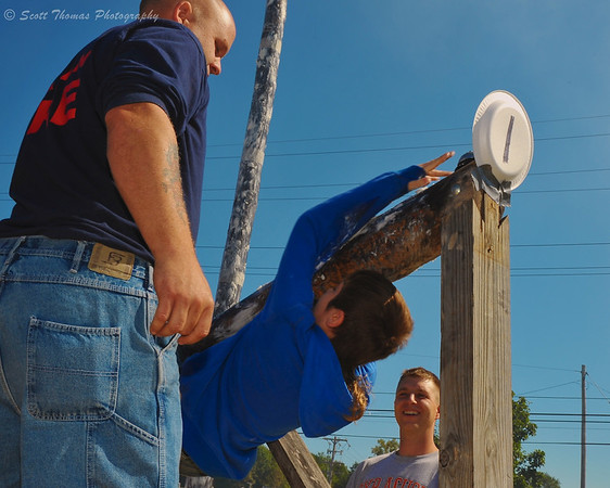 A boy hangs on as he reaches up to ring the bell during the Kid's Greased Pole Cross at the Jordan Fall Festival in Jordan, New York.