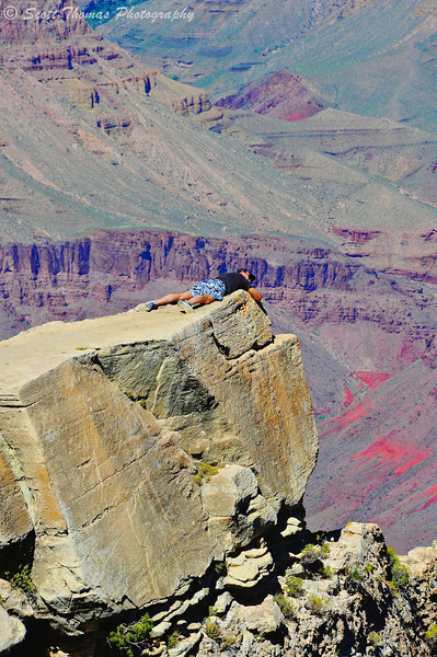 Man clinging to a rock ledge at the Grand Canyon National Park in Arizona.