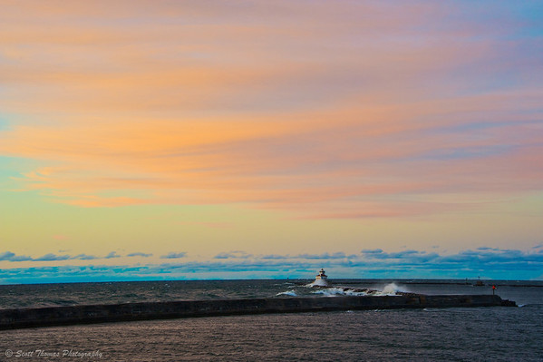 A setting Sun lights up the sky above the breakwall in the Oswego, New York harbor.