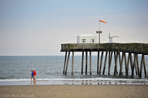 A couple walking past a wooden pier near the Ocean City Boardwalk on the Atlantic Ocean shore in New Jersey.