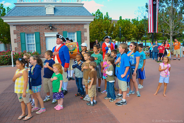 Members of the Spirit of America Fife and Drum Corps lead young guests in the Pledge of Allegiance in front of the American Adventure in Epcot's World Showcase.