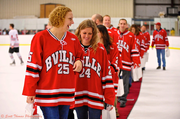 Teachers with their gift bags, walk off the ice after the Teacher Appreciation Ceremony.