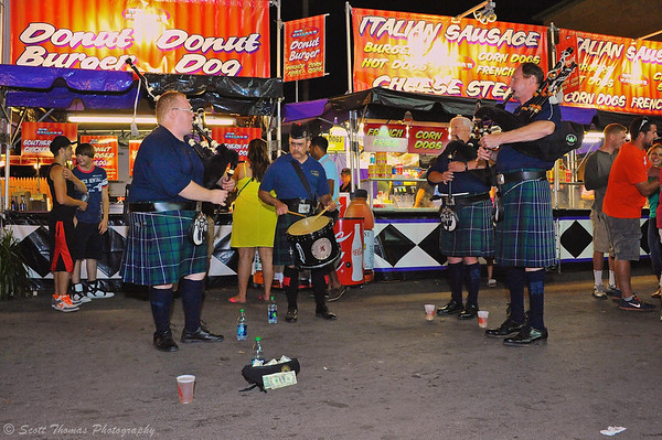 Irish bagpipers and drummer playing for tips in front of a food vendor at The Great New York State Fair in Syracuse, New York.