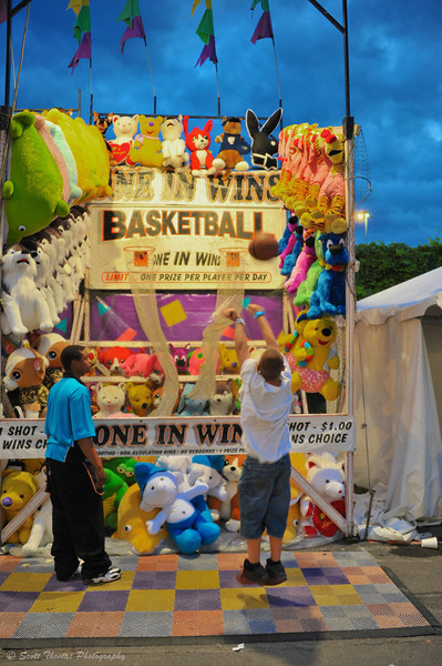 A young boy tries to make a basket at a Midway game during the Great New York State Fair.