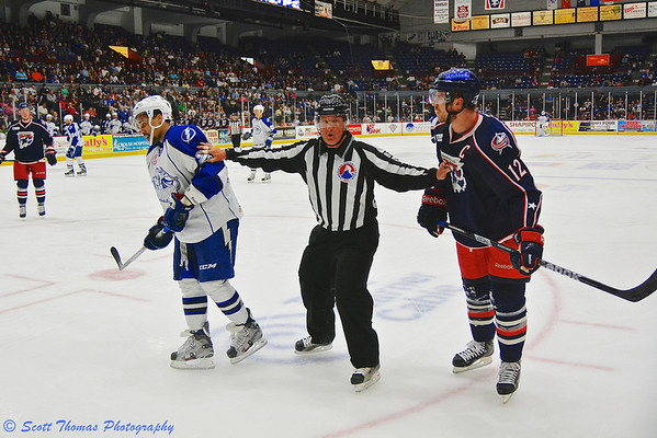 AHL Linesman separates Syracuse Crunch J. T. Brown (23) and Springfield Falcons Ryan Craig (12) in American Hockey League (AHL) Calder Cup Playoff action at the Onondaga County War Memorial on Wednesday, May 15, 2013.