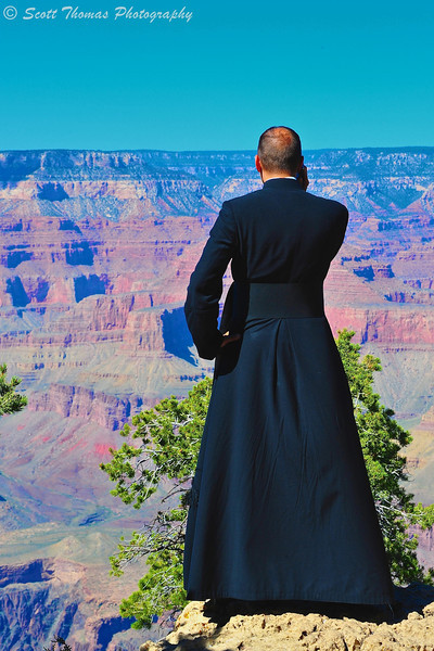 A Priest talking on his cell phone along the South Rim Trail near Yavapai Point at the Grand Canyon National Park in Arizona.