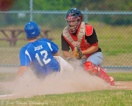 A CNY Americans player scores sliding into home plate against the Ottawa Canadian catcher in CNY Thunder Classic action in Rome, New York.