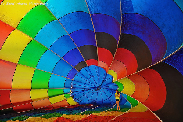 A young woman inside a rainbow colored hot air balloon at the Oswego Balloonfest at the Oswego Country Fairgrounds in Sandy Creek, New York.