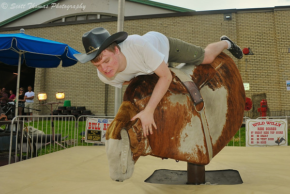 A man about to be dumped off of Wild Willy, a mechanical bull, at The Great New York State Fair in Syracuse, New York on Saturday, August 23, 2014