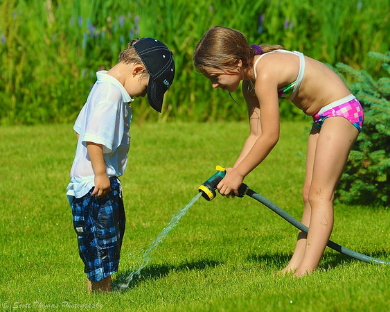 Girl spraying her young cousin's feet with a water hose.