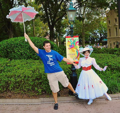 A guest on holiday poses with Mary Poppins and her umbrella at the United Kingdom pavilion in Epcot's World Showcase, Walt Disney World, Orlando, Florida.