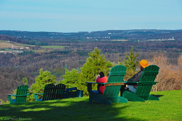 People enjoying the view from green Adirondack chairs near the Skyline Lodge at Highland Forest in Fabius, New York.