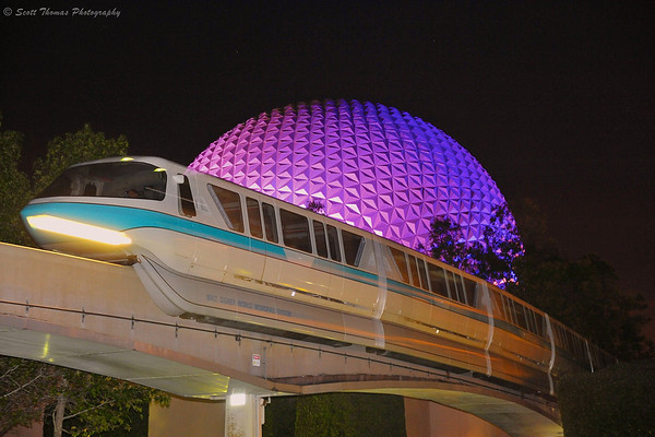 Monorail Blue entering Epcot at night past Spaceship Earth in Walt Disney World.