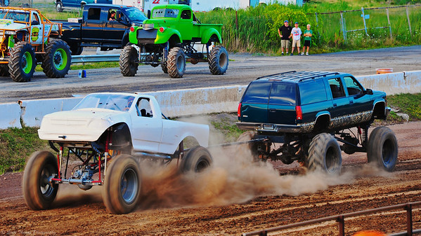 Monster trucks spin their wheels in a game of Tug-O-War at the 13th annual Syracuse Nationals Car Show in front of the Grandstand of  the New York State Fairgrounds.