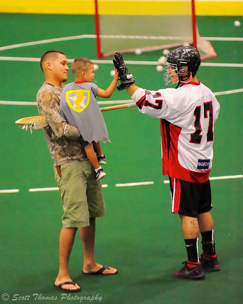 Onondaga Redhawks Andy Jamerison (17) greets a young fan before playing the Newtown Golden Eagles in the Can-Am Senior