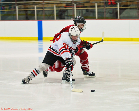 Baldwinsville Bees Matt Zandri (22) protects the puck from a Central Square Redhawks defender.
