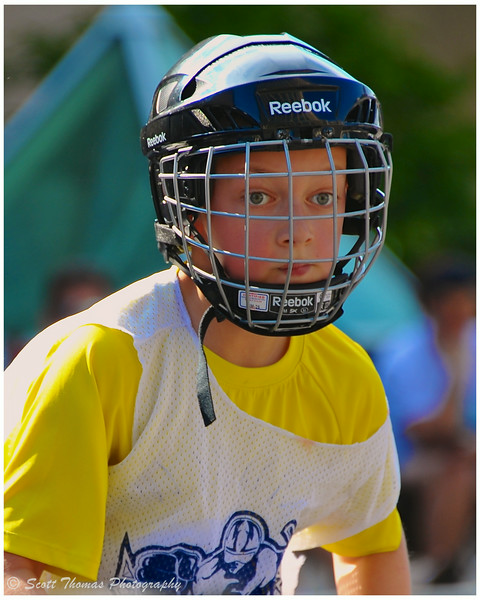 A young boy watching the play and waiting for a pass during the Street Crunch hockey game outside the War Memorial Arena in Syracuse, New York on Saturday, July 26, 2014.