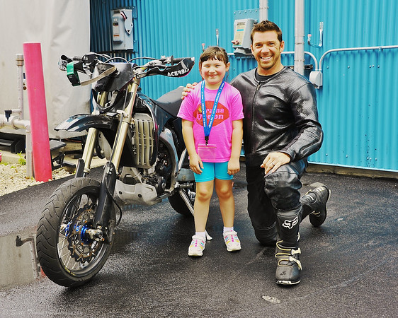 A young Photowalk participant poses with a stunt driver backstage at the Lights, Motors, Action Extreme Stunt Show in Disney's Hollywood Studios.
