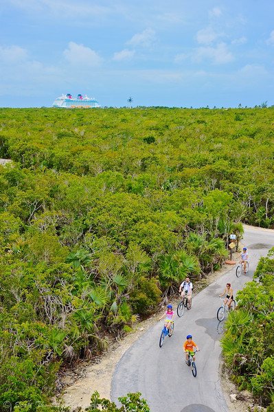 A family riding rented bicycles on the bike trail at Castaway Cay on a Disney Dream cruise.