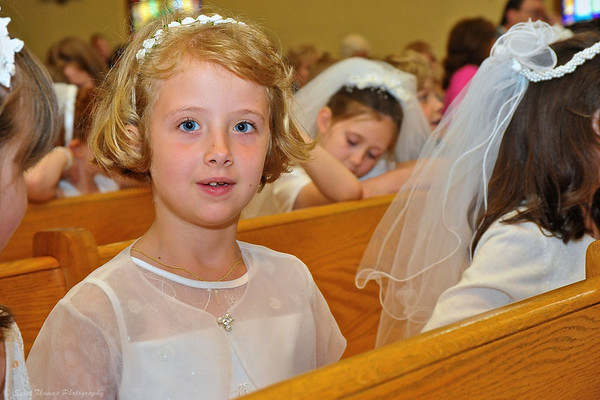Young girl curious about my camera during her First Communion ceremony at the St. Francis Xavier Church in Marcellus, New York.