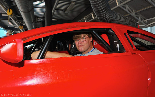 Scott behind the wheel of the red Hero car backstage at the Lights, Motors, Action Extreme Stunt Show in Disney's Hollywood Studios.