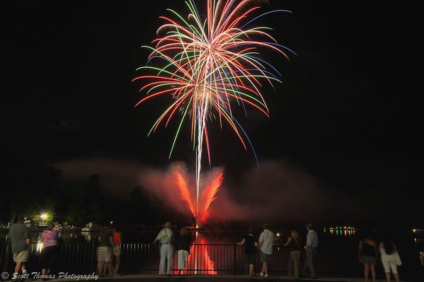 Members of the Alumni of the C. W. Baker High School watch fireworks from Paper Mill Island in Baldwinsville, New York.