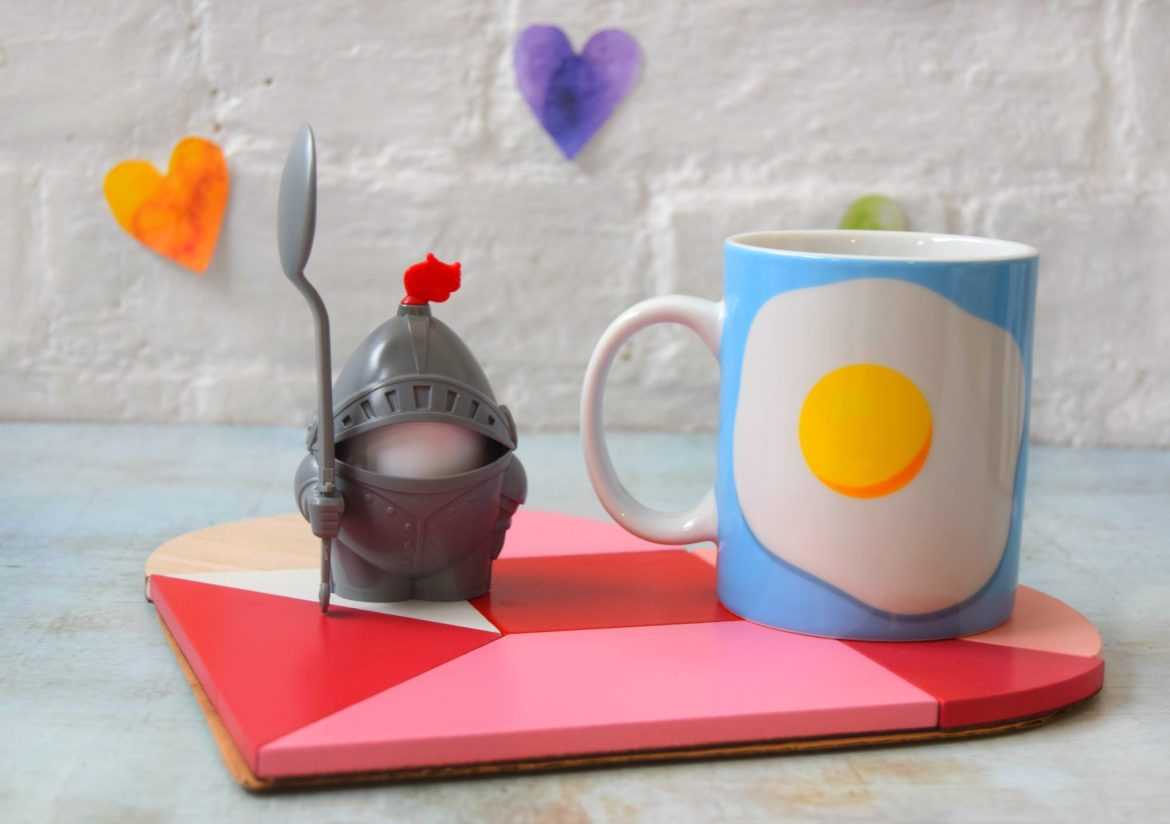 Breakfast in bed set. A heart coaster, a novelty knight egg cup and spoon and a blue mug with a fried egg on.