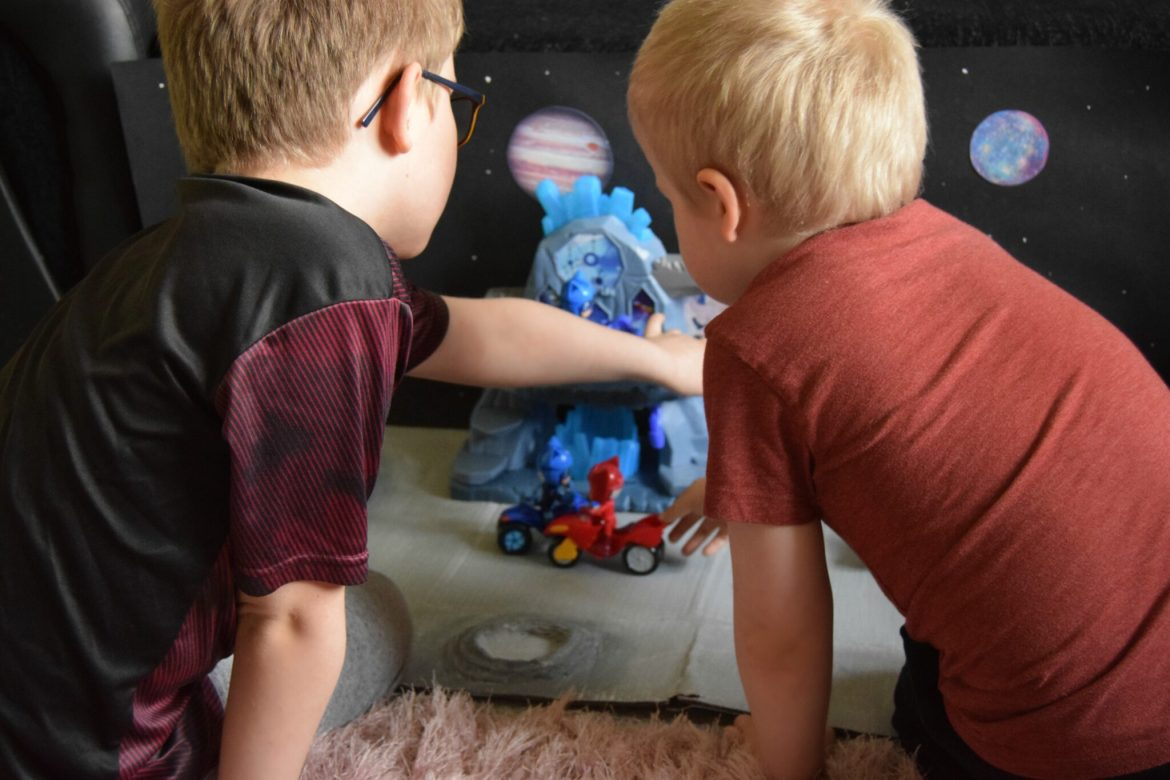 The boys playing with their Super Moon fortress playset and Pj Masks craft space background.