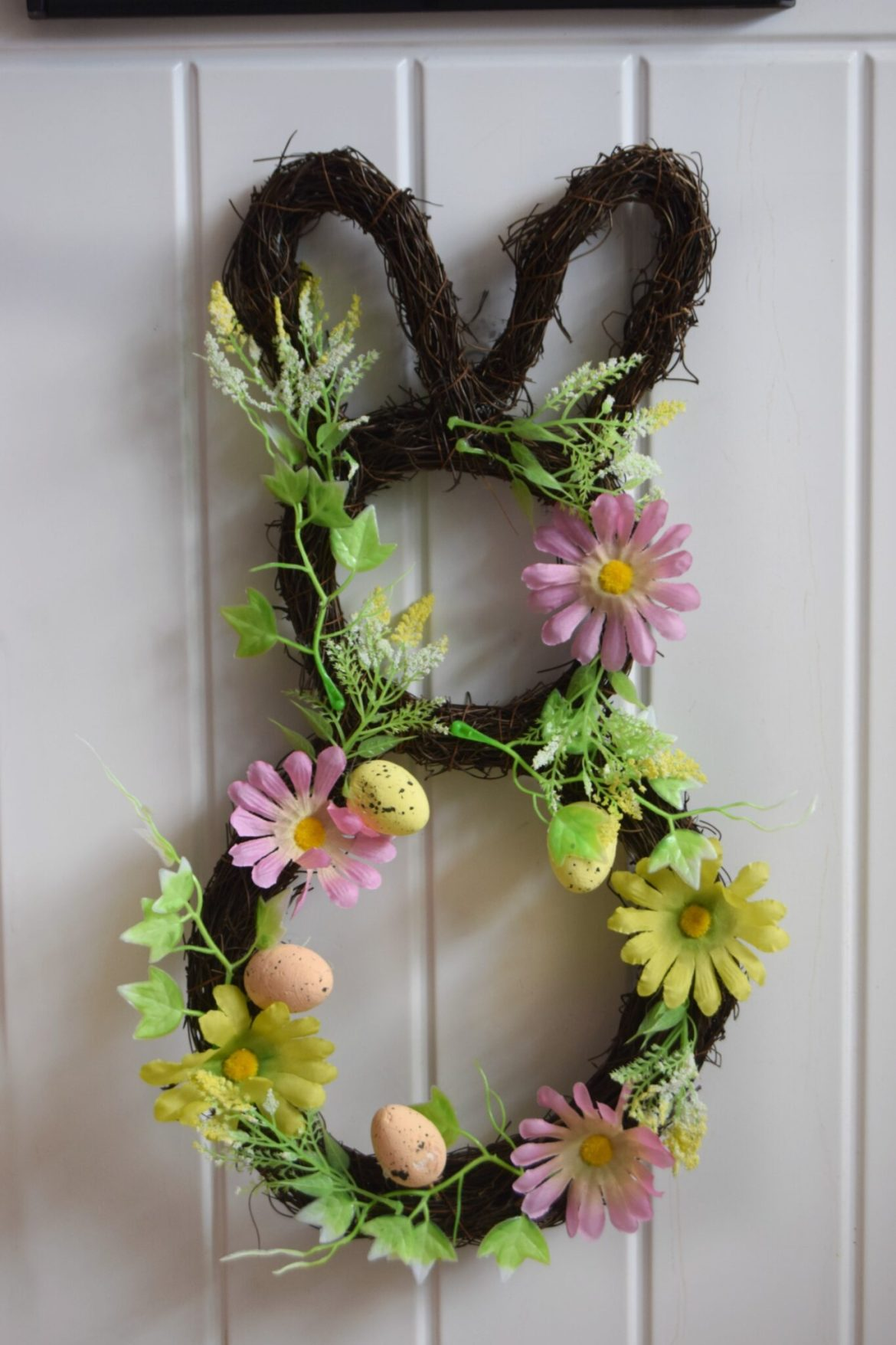 Bunny wreath decorated with spring flowers and easter eggs.