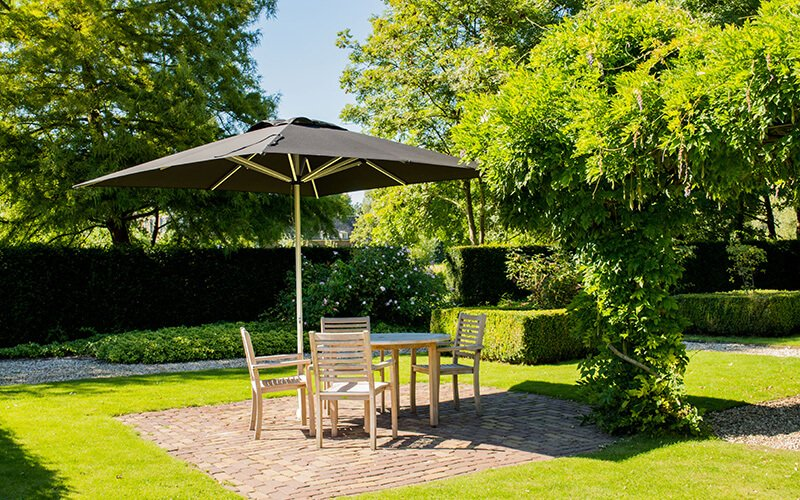 Garden accessories for the summer. A patio parasol with table and chairs.