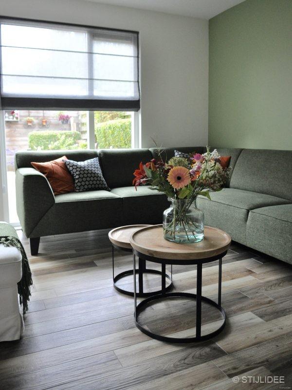 Binnenkijken in  een woonkamer met een groene hoekbank