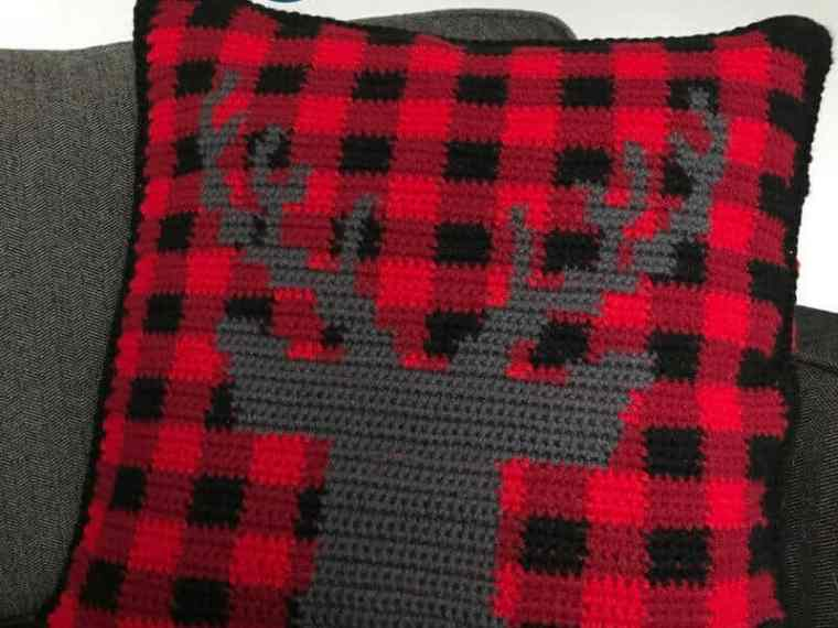 Wow! What a cute buffalo check crochet pillow cover. Get in the holiday spirit with this free crochet pattern. Plaid plus a stag – couldn't get any trendier. #RHSS #CrochetChristmas #Christmasdecor
