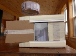 """Dream Lightbox"" maquette. Cardboard, masking tape, plastic packaging window, NY Times photo printed on white copy paper."
