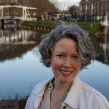 portrait photo of Susan with canals and bridge behind
